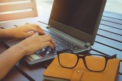 Mani che lavorano al computer portatile con i vetri ed il taccuino Immagine Stock Libera da Diritti