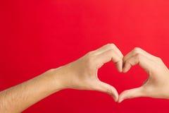 Mani che modellano in un cuore fotografia stock