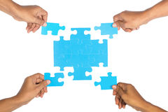 Mani che montano puzzle. Fotografia Stock Libera da Diritti