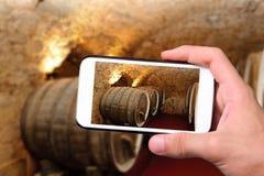 Mani che prendono a foto i vecchi barilotti di vino con lo smartphone Fotografia Stock