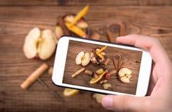 Mani che prendono a foto la sangria del vino rosso con le mele e le arance con lo smartphone Immagini Stock