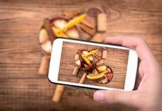 Mani che prendono a foto la sangria del vino rosso con le mele e le arance con lo smartphone Fotografia Stock