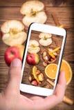 Mani che prendono a foto la sangria del vino rosso con le mele e le arance con lo smartphone Immagini Stock Libere da Diritti