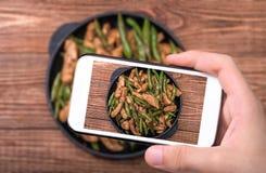 Mani che prendono a foto pollo casalingo con asparago con lo smartphone Fotografia Stock