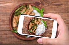 Mani che prendono a foto pollo casalingo con asparago con lo smartphone Immagini Stock