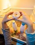 Mani che prendono grande ciambella dallo scaffale superiore del frigorifero Fotografia Stock