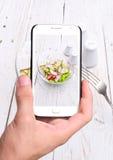 Mani che prendono l'insalata del ravanello della foto con lo smartphone Immagine Stock