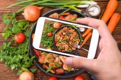 Mani che prendono la carne della foto con le verdure con lo smartphone Fotografia Stock