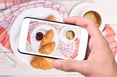 Mani che prendono la tazza di caffè della foto con i croissant con lo smartphone Fotografie Stock