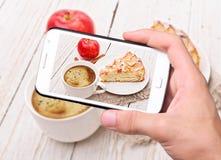 Mani che prendono la torta di mele della foto con lo smartphone Fotografia Stock