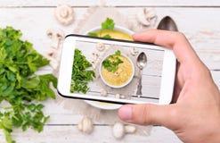 Mani che prendono la zuppa di fungo della foto con lo smartphone Fotografia Stock