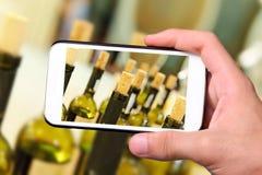 Mani che prendono le bottiglie di vino della foto con lo smartphone Fotografie Stock