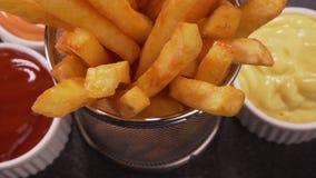 Mani che prendono le patate fritte deliziose servite in un piccolo canestro di frittura stock footage