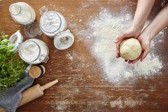 Mani che presentano a pasta della pasta tavola e farina di legno Fotografia Stock Libera da Diritti
