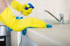 Mani che puliscono il controsoffitto della cucina Immagini Stock Libere da Diritti