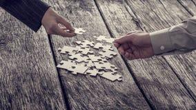 Mani che raggiungono per i pezzi di puzzle Immagine Stock