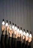 Mani che raggiungono per le lampadine Immagine Stock