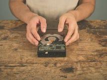 Mani che riparano un azionamento duro sullo scrittorio Fotografia Stock Libera da Diritti