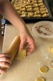 Mani che rotolano pasta per i biscotti Fotografie Stock