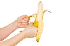 Mani che sbucciano una banana fresca Fotografia Stock