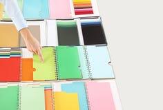 Mani che scelgono un colore dal campionatore Immagine Stock