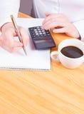 Mani che scrivono con il caffè ed il calcolatore, progettanti Immagine Stock