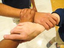 Mani che si tengono nell'unità di lavoro di squadra fotografie stock libere da diritti
