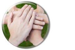 Mani che si uniscono nella sfera di vetro su fondo bianco Fotografia Stock
