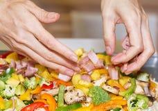 Mani che sistemano gli ortaggi freschi e carne Fotografia Stock
