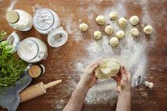 Mani che srotolano vista della pasta da sopra la scena viva della cucina Fotografia Stock