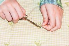 Mani che tagliano filo con le forbici Fotografia Stock