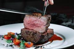 Mani che tagliano la bistecca del filetto sul piatto con insalata Fotografia Stock