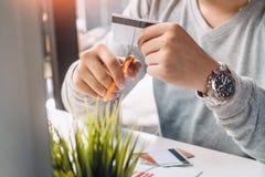 Mani che tagliano la carta di credito con le forbici Immagine Stock Libera da Diritti