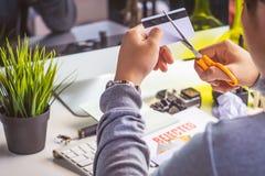 Mani che tagliano la carta di credito con le forbici Immagini Stock