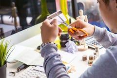 Mani che tagliano la carta di credito con le forbici Fotografie Stock Libere da Diritti