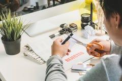 Mani che tagliano la carta di credito con le forbici sullo scrittorio funzionante del fotografo con la lente di DSLR, la lettera  Fotografia Stock