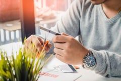 Mani che tagliano la carta di credito con le forbici sullo scrittorio funzionante del fotografo con la lente di DSLR, la lettera  Fotografie Stock