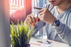 Mani che tagliano la carta di credito con le forbici sullo scrittorio funzionante del fotografo con la lente di DSLR, la lettera  Immagini Stock