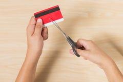 Mani che tagliano una carta di credito con le forbici Fotografia Stock