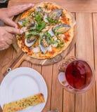 Mani che tagliano una pizza dei frutti di mare con la Nuova Zelanda NZ m. lipped verde Fotografie Stock