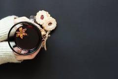 Mani che tengono bicchiere di vino di vino caldo con la vista superiore dei biscotti Fotografie Stock Libere da Diritti