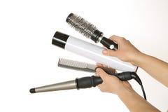 Mani che tengono capelli e gli accessori d'arricciatura Fotografia Stock