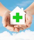 Mani che tengono casa di carta con l'incrocio verde Immagine Stock
