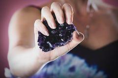 Mani che tengono cristallo ametista porpora immagini stock libere da diritti