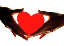 Mani che tengono cuore Fotografie Stock