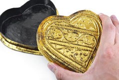 Mani che tengono cuore dorato Immagine Stock