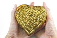 Mani che tengono cuore dorato Fotografia Stock