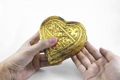 Mani che tengono cuore dorato Immagini Stock