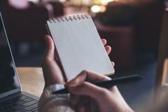 Mani che tengono e che scrivono su un taccuino in bianco con il computer portatile del computer sulla tavola Fotografia Stock Libera da Diritti