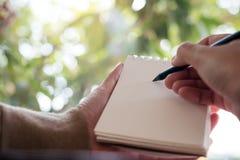 Mani che tengono e che scrivono su un taccuino in bianco con il fondo della natura della sfuocatura Immagini Stock